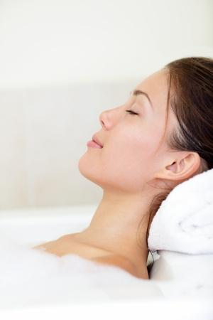 Spa vrouw ontspannen in bad ontspannen en serene met gesloten ogen Stockfoto