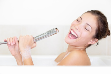 lying in bathtub: Bath woman singing in bathtub using shower head having fun Stock Photo
