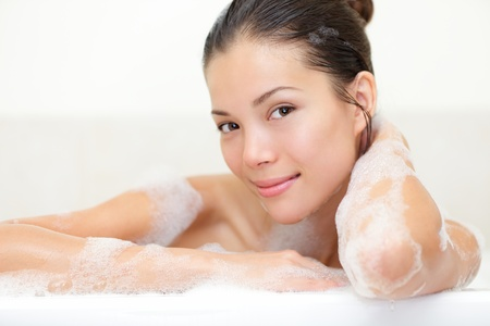 Beauty portrait of woman in bathtub with bath foam smiling happy looking serene at camera photo