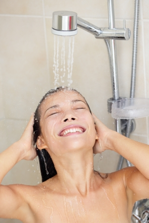 Woman washing hair enjoying showering smiling happy with face under running water. Beautiful mixed race Caucasian  Asian Chinese model in her twenties.