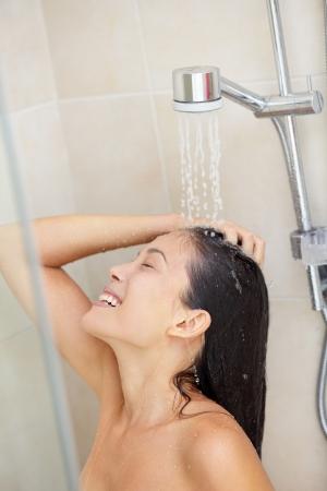 Lavado del cabello. Ducha lavado ducharse mujer pelo disfrutando bajo las salpicaduras de agua. Feliz sonriente bastante multirracial Asia / caucásica modelo femenino en casa en el baño. Modelo de unos 20 años. Foto de archivo - 16793350