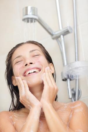 Woman Waschen des Gesichts in der Dusche. Duschen asiatische Frau genießen Spritzwasser im Gesicht während der Reinigung Gesicht. Portrait der multiethnischen asiatische  Caucasian Mädchen lächelnd glücklich. Model in ihren 20ern. Lizenzfreie Bilder