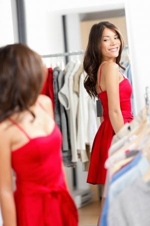 Vrouw winkelen op zoek in spiegel probeert kleding jurk in kledingwinkel. Jonge mooie multiculturele vrouw proberen op rode jurk in paskamer. Gemengd ras Kaukasische Aziatische meisje in haar twintiger jaren.