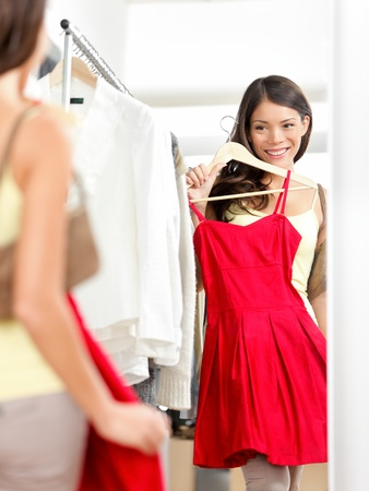 trying: Shopper woman trying clothing dress while shopping in clothes store during sale. Beautiful young multicultural Asian  Caucasian female model smiling happy and joyful.