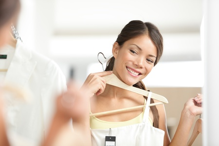 Young woman shopper looking at dress in mirror smiling happy Stock Photo