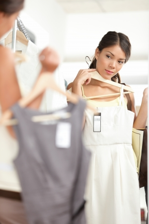 Woman shopping choosing dresses looking in mirror uncertain. Beautiful young multicultural shopper in clothing store. Stock Photo - 17892533