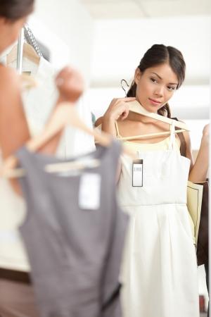 Woman shopping Wahl Kleider suchen im Spiegel ungewiss. Schöne junge multikulturelle Shopper in Bekleidungsgeschäft.