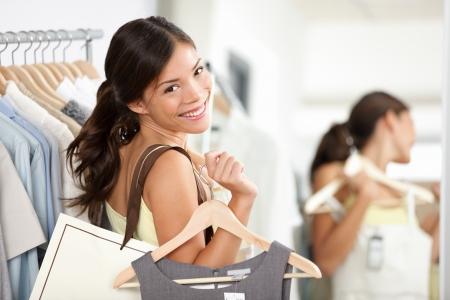 Happy shopping vrouw in kledingzaak lachend bedrijf boodschappentassen en kleding jurk. Mooie Euraziatische model binnen Stockfoto