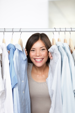 Small business clothing shop owner portrait in store. Funny image of woman clothes shop owner peeping through shirts smiling happy and excited at camera. Multicultural Asian Caucasian female model indoors. photo