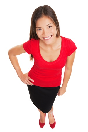 Schöne stilvolle Frau mit Charme lächelnd in die Kamera mit einem schönen breiten Lächeln, als sie mit ihrer Hand stellt auf ihrer Hüfte in einem Ganzkörper hohen Winkel Porträt auf weißem asiatischen kaukasischen Mädchen isoliert