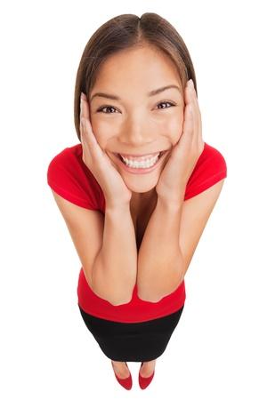 Gelukkige vrouw te overwinnen met vreugde houdt haar handen op haar wangen als ze kijkt omhoog naar de camera lens met een mooie glimlach, hoge hoek full length studio portret op witte achtergrond multiculturele model