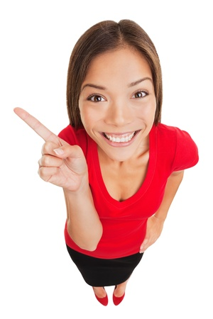 Pointing showing woman  Humorous high angle studio portrait of a grinning woman pointing to the left of the frame with her finger  Mixed race Asian Caucasian business woman isolated on white background