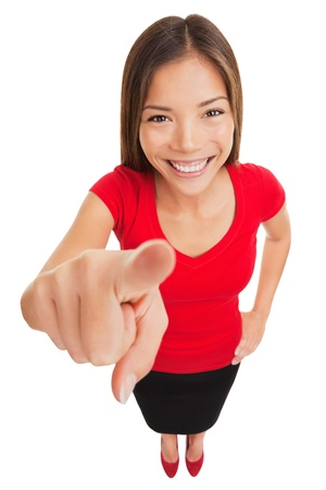 identifies: Pointing woman  Attractive smiling woman pointing directly at the camera with her finger as she makes her selection or identifies a person, funny high angle full length portrait isolated on white  Stock Photo