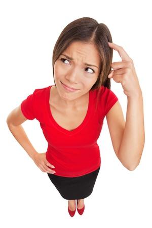 Gekeusd denkende vrouw Grappige hoge hoek studio portret van een verbijsterde en verwarde vrouw haar hoofd krabben als ze zoekt een oplossing die op witte achtergrond multi-etnische vrouwelijke model Stockfoto