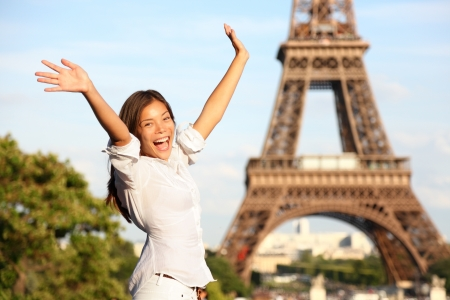 Happy tourist on travel holidays cheering joyful with arms raised up excited at Paris Eiffel Tower Standard-Bild