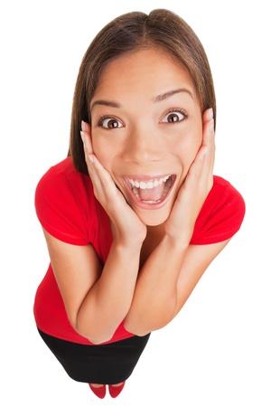 Joyful opgewonden verrast jonge vrouw houdt haar handen op haar wangen lachend omhoog