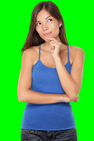 Thinking young woman looking at copy space. Beautiful pensive mixed race Caucasian  Chinese Asian girl isolated on green background in blue tank top.