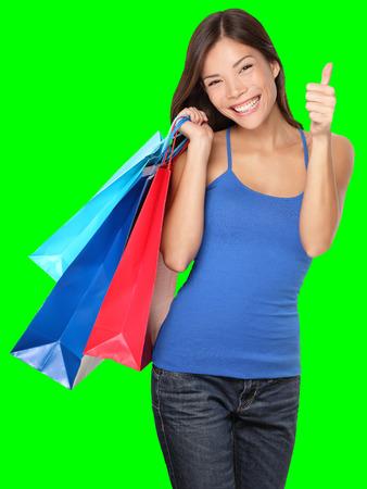 Einkaufen Frau zeigt Daumen hoch Erfolg halten Einkaufstüten auf grünem Hintergrund. Schöne junge gemischte Rasse asiatischen Caucasian Frau Shopper.