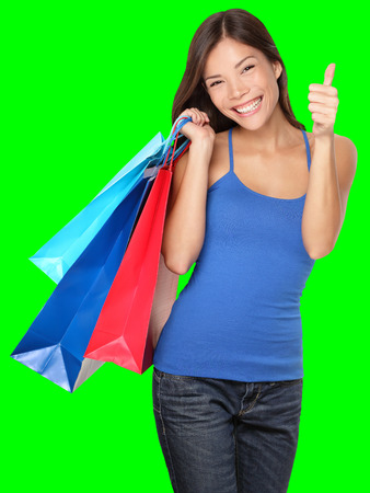 Shopping woman showing thumbs up success holding shopping bags isolated on green background. Beautiful young mixed race Asian Caucasian female shopper. Archivio Fotografico