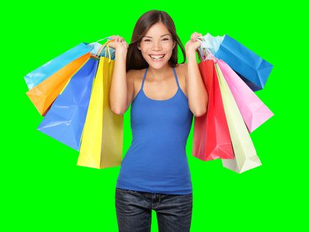 Shopper Frau mit Einkaufstüten. Junge schöne Frau während der Shopping-Verkauf halten viele bunte Einkaufstaschen isoliert auf Green-Screen-Chroma-Key-Hintergrund.