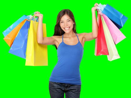 Einkaufen Frau mit Einkaufstüten über dem Kopf lächelnd während Verkauf Einkaufsbummel zufrieden. Schöne junge weibliche Shopper isoliert auf grünem Hintergrund. Lizenzfreie Bilder