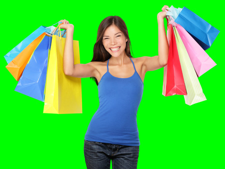 arms above head: Shopping woman holding shopping bags above her head smiling happy during sale shopping spree. Beautiful young female shopper isolated on green background. Stock Photo