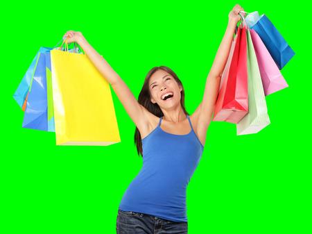 Happy shopping Frau aufgeregt und fröhlich in freudiger Glückseligkeit. Shopper mit bunten Einkaufstüten isoliert auf Green-Screen-Chroma-Key-Hintergrund. Beschwingt schönen kaukasischen Asiatisch Chinesisch weiblichen Modell.