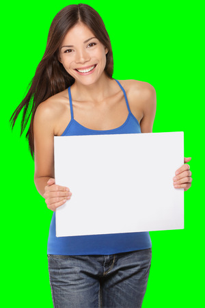 Woman showing blank paper sign whiteboard. Fresh, happy and joyful multiracial girl in her twenties showing copy space for your message. Isolated on green screen chroma key background in studio.