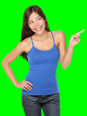 Woman pointing happy showing and looking to the side - Isolated on green screen chroma key background. Beautiful young multiracial Caucasian / Chinese Asian female model in studio. Stock Photo