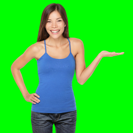 Woman showing your product or message smiling happy Isolated on green screen chroma key background. Beautiful multi-racial girl in blue tank top showing open hand palm. Archivio Fotografico