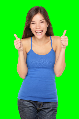 Happy woman giving thumbs up success hand sign smiling joyful and happy. Pretty young multiracial Asian  Caucasian female model in tank top. Isolated on green screen chroma key background. Stock Photo
