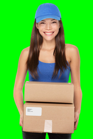Delivery person holding packages wearing blue cap. Woman courier smiling happy isolated on green screen chroma key background.. Beautiful young mixed race Caucasian / Chinese Asian female professional.
