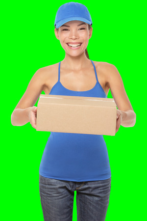 Female package delivery person giving packages wearing blue uniform. Woman courier smiling happy isolated on green screen chroma key background. Young mixed race Caucasian Chinese Asian female courier photo