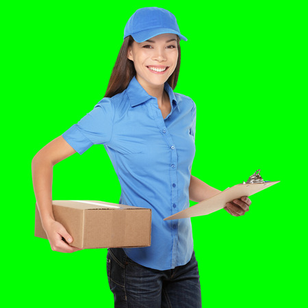 Delivery person delivering packages holding clipboard and package smiling happy in blue uniform. Beautiful young Caucasian Chinese Asian female courier. Isolated on green screen chroma key background. Archivio Fotografico