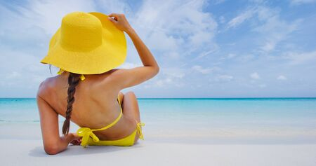 Woman on beach vacation lying in sand with beach hat sunbathing by perfect turquoise ocean. Elegant young adult on woman for tropical travel luxury holidays. Archivio Fotografico