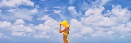 Banner - Beach travel elegant woman on beach walking enjoying summer luxury travel walking in bikini wearing beach hat. Pretty stylish lady.