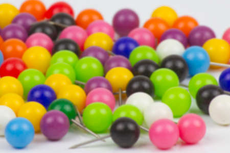 Colorful push pins on white background.