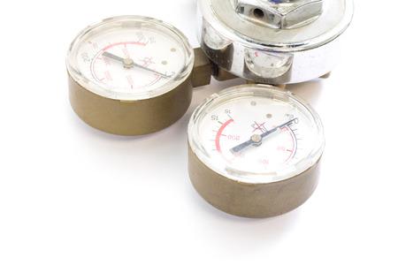 Reguladores de presión de gas en un equipo analítico de laboratorio sobre un fondo blanco.