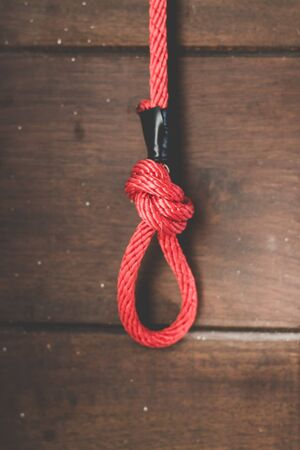 Red Rope knot on old wooden board background.