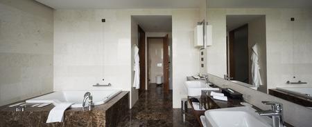 foto de archivo moderno bao interior con doble lavabo y espejos grandes tina de bao azulejos ventana de vista y toallas