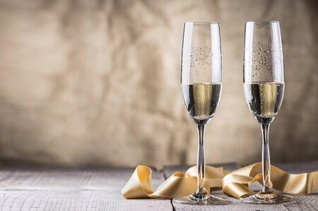 due bicchieri di champagne con nastro d'oro su tavola di legno. Valentino