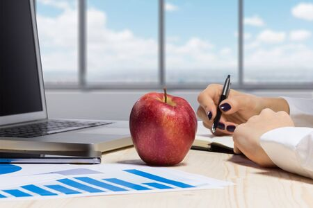 tabla de surf: Business woman in an office holding red apple - Clipping Path Foto de archivo