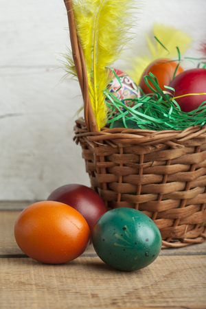 Easter eggs in basket and natural wooden country table copyspace