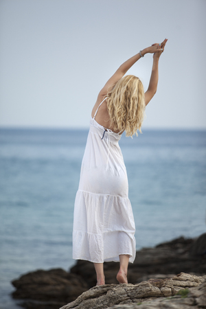woman practicing yoga and relaxing on the beach