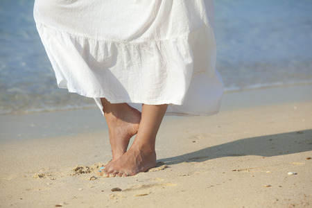barefooted woman walking on beach 스톡 콘텐츠