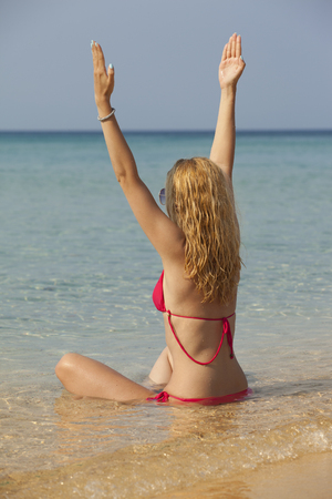 young woman with beautiful blonde hair meditating in sea 스톡 콘텐츠