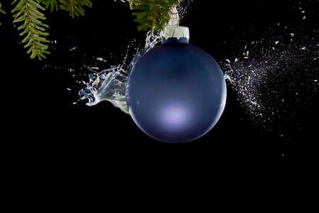 Christmas ball braking. Liquid splashing out. Stock Photo