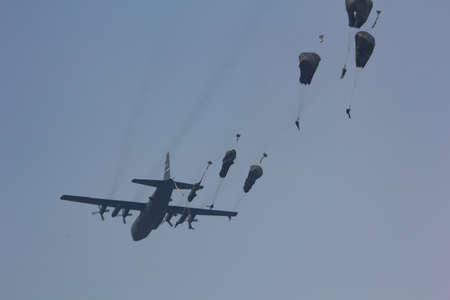Ede, The Netherlands - September 20 2014: Paratroopers jumping from a C-130 Hercules aircraft over the Ginkel Heath, during the Garden Market Memorial.