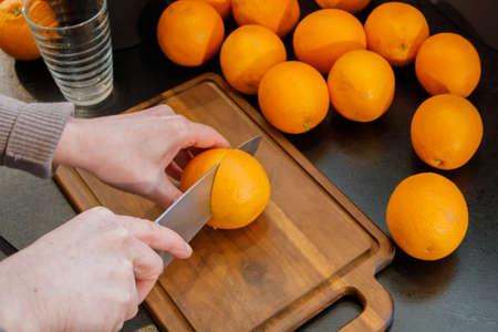 Slicing an orange to make fresh orange juice. Healthy lifestyle comcept Stock Photo