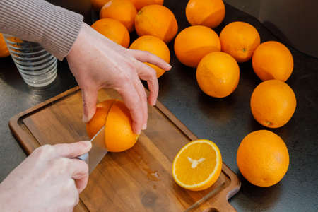 Cutting an orange to make fresh and healthy orange juice. Healthy lifestyle concept.